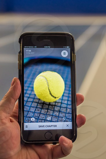 Hand holding a cell phone with a picture of a tennis ball within the SCRIBA APP in front of a tennis court. photo