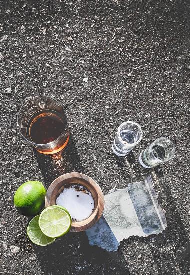 clear rocks glass with tequila near lemon fruit and salt photo