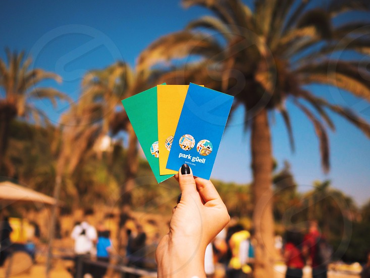 Park Guell in Barcelona. Woman's hand holding three colorful tickets on palm trees background. photo