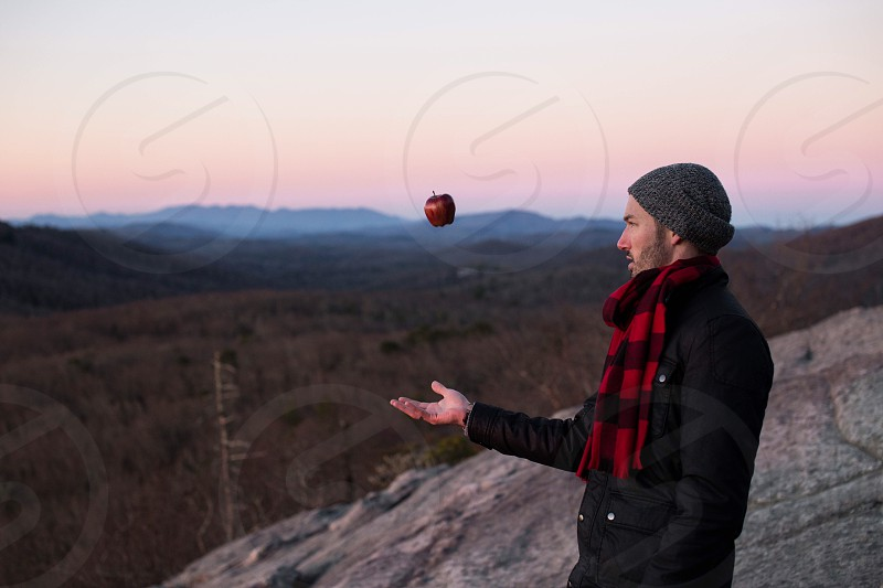 man in black coat tossing apple in front of him standing on stone near on green mountain during golden hour photo