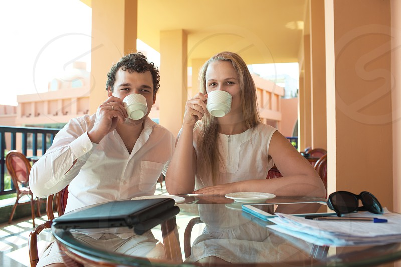 Young couple drinking coffee on an outdoor balcony sitting together with their cups raised to their mouths as they relax and enjoy the view and the summer sunshine photo