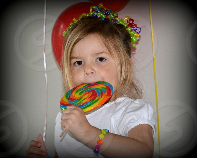 girl in white shirt licking large multicolor lollipop photo