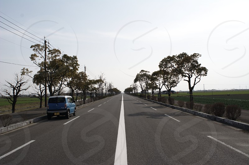 blue vehicle driving on gray asphalt road under gray sunny sky photo