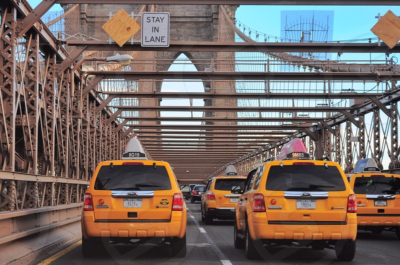 yellow ford escapes on Brooklyn bridge during daytime photo