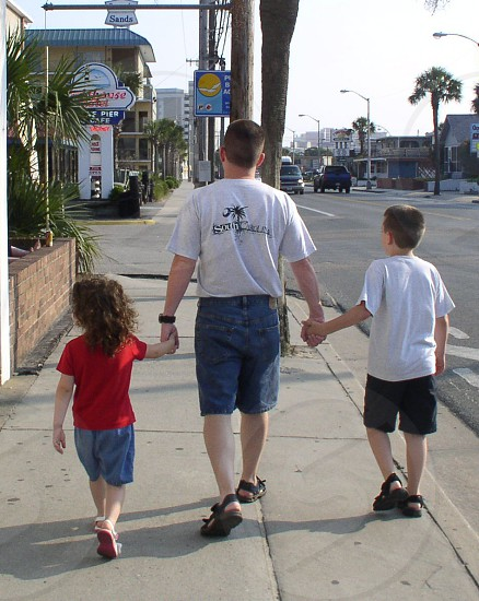 Father and children walk down the street photo