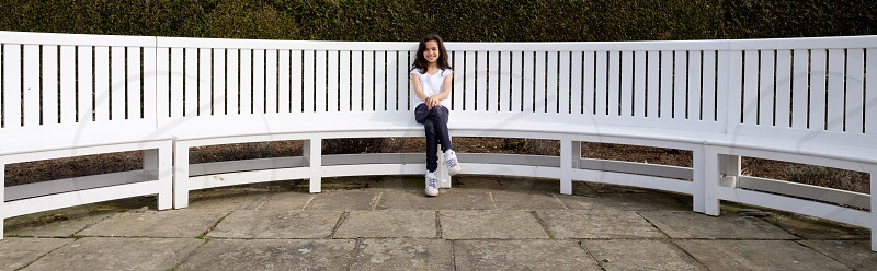 Panoramic portrait of a little girl sitting on a long white garden bench with her hands on her knees and crossed legs wearing blue leggingswhite top and white trainers photo