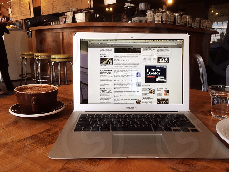 silver macbook air next to cup of coffee photo