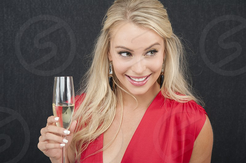 Pretty Blonde with Champagne glass smiling. Red dress dark grey textured background  photo