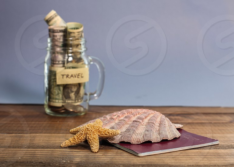 Saving money for travel in jar with shell and starfish photo