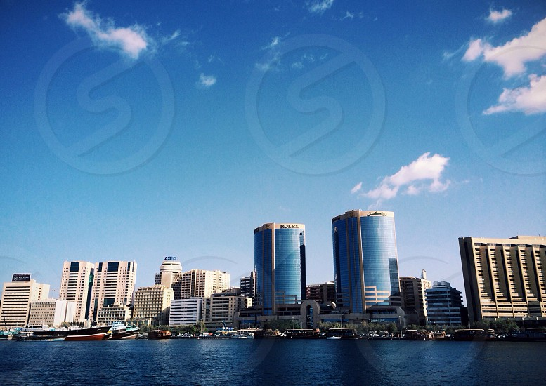 city skyline beside body of water under clear sky during daytime photo