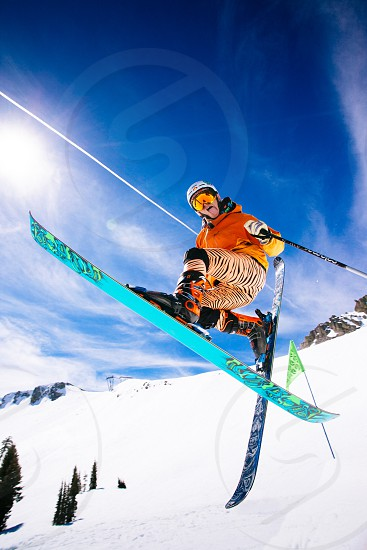 Skier making a jump with blue sky and white snow photo