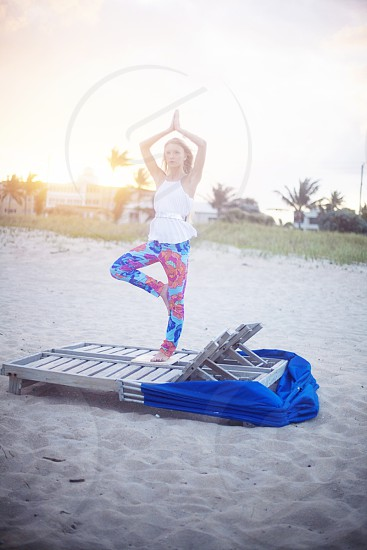 woman in white tank top standing on lounger doing yoga position photo