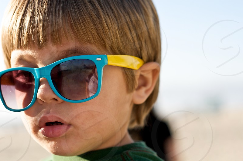 A toddler wearing sunglasses on the beach in Venice photo