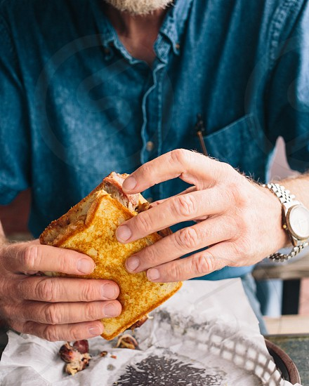 man in blue denim shirt holding toasted sanwdwich photo