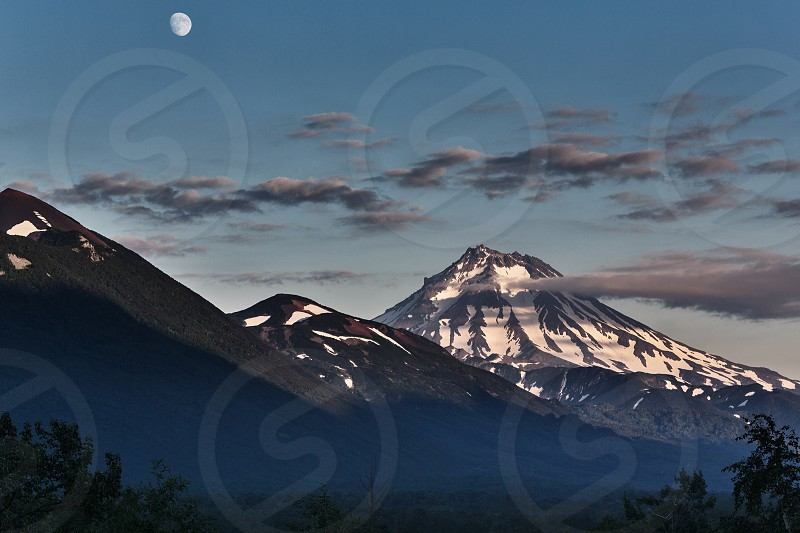 Beautiful mountain landscape of Kamchatka Peninsula: evening view of Vilyuchinsky Volcano and moon. Russia Far East. photo