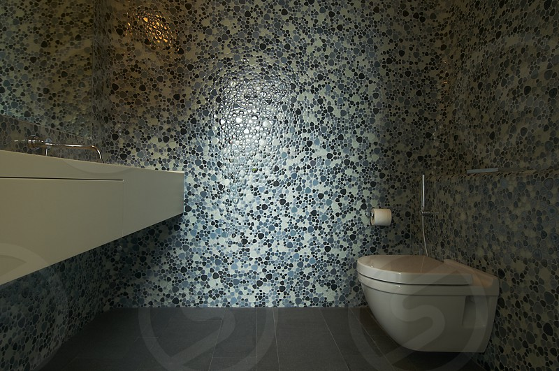 Beautiful designer toilet with small mosaic tiles on the walls photo