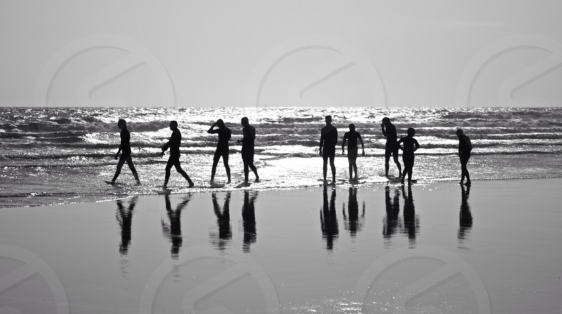 group of people walking on seashore photo