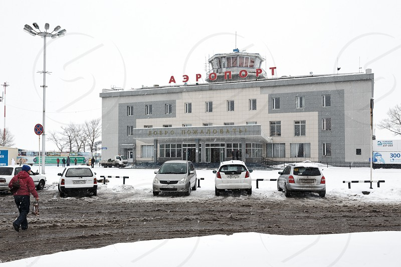 PETROPAVLOVSK-KAMCHATSKY KAMCHATKA RUSSIA - MARCH 19 2015: Winter view of commercial airport terminal Petropavlovsk-Kamchatsky and parked cars on the station square. Far East Kamchatka Peninsula. photo