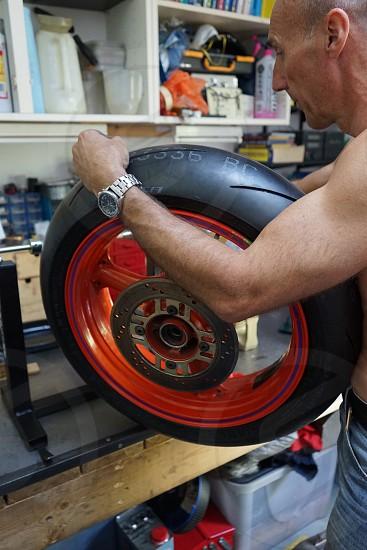 Man in workshop working on motorbike wheel and tyre photo
