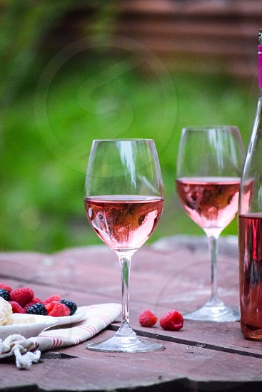 close up photo of 2 filled wine glass and clear glass bottle on top of red wooden table photo