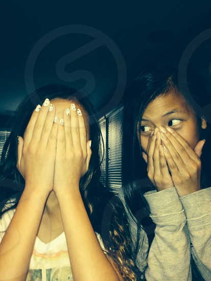 2 girls cover their face with hands photo