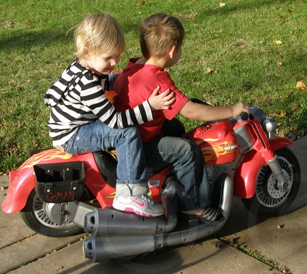 Hold on baby! Two toddlers on a red battery powered motorcycle on a spring day! photo