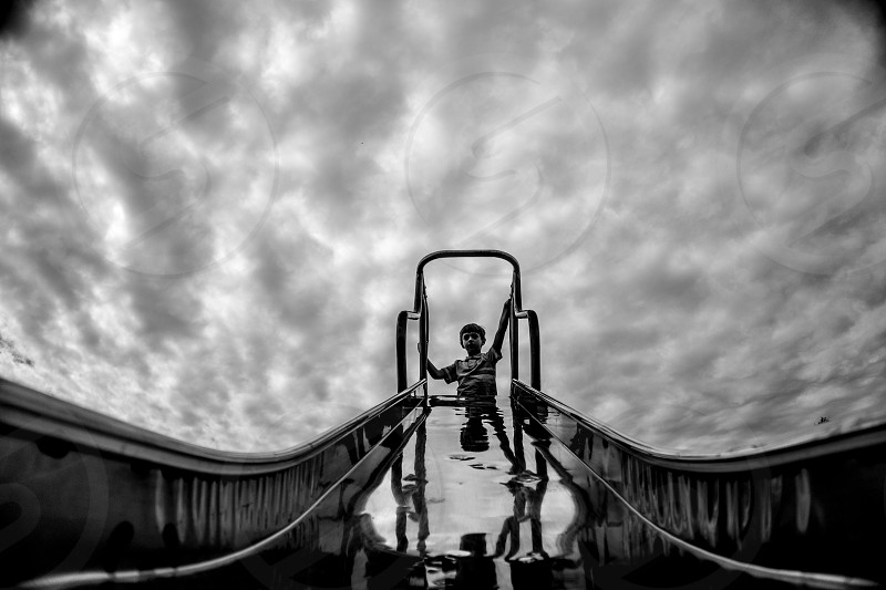 boy on top of slide bottom view in grayscale photo