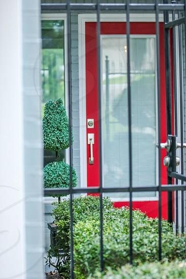 Red front door seen through gate photo