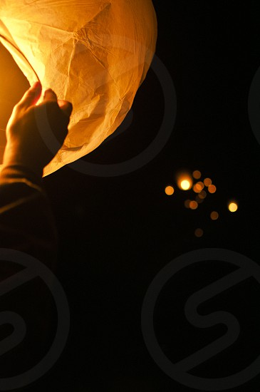 view of flying paper lanterns during night photo