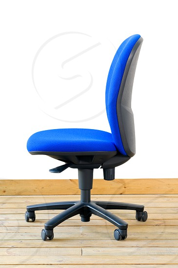 modern blue office chair on wood floor over white background photo