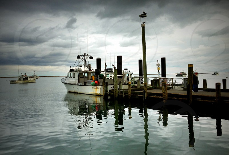 fishing boats at end of dock under cloudy sky photo