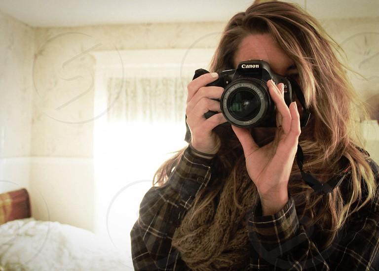 woman in gray black white plaid long sleeved shirt taking a photo using black canon dslr camera photo