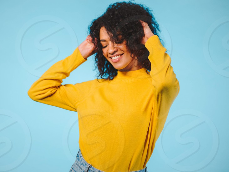 Close up portrait of laughing african american woman isolated on blue background. Mix raced girl in yellow wear posing in studio. photo