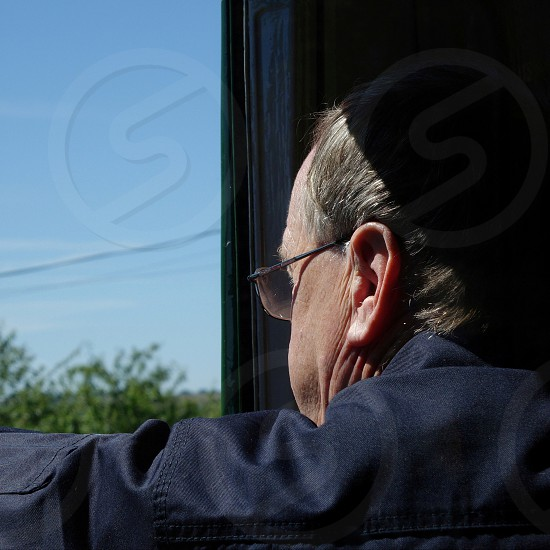 Image of a train drivers head from the rear looking sideways out of train window... photo
