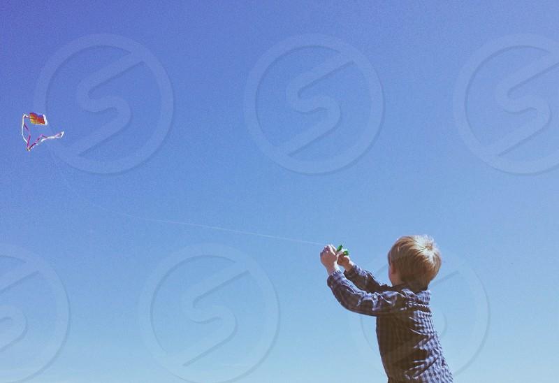 Boy flying a kite.  photo