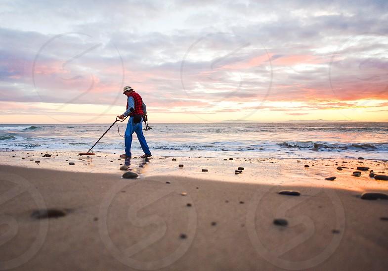 treasure hunter man metal detector seeker finder look search jewelry beach sunset photo
