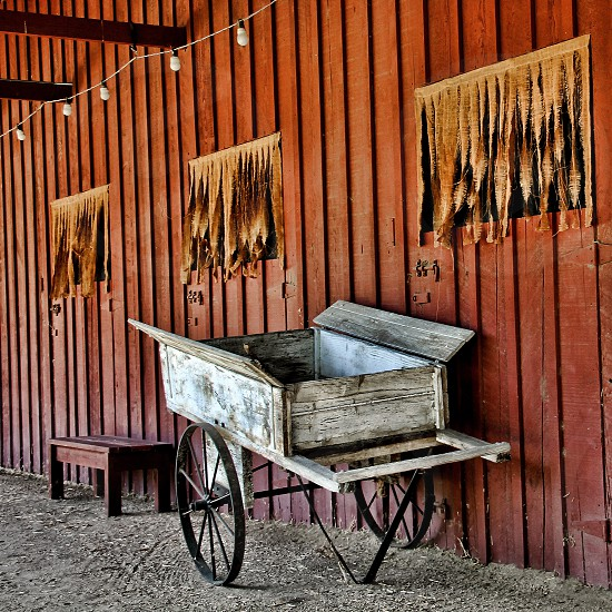 Small wooden cart next to a red wooden barn photo
