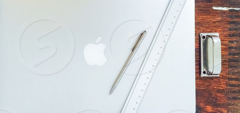 Desk with laptop pen ruler next to a steel handle. photo