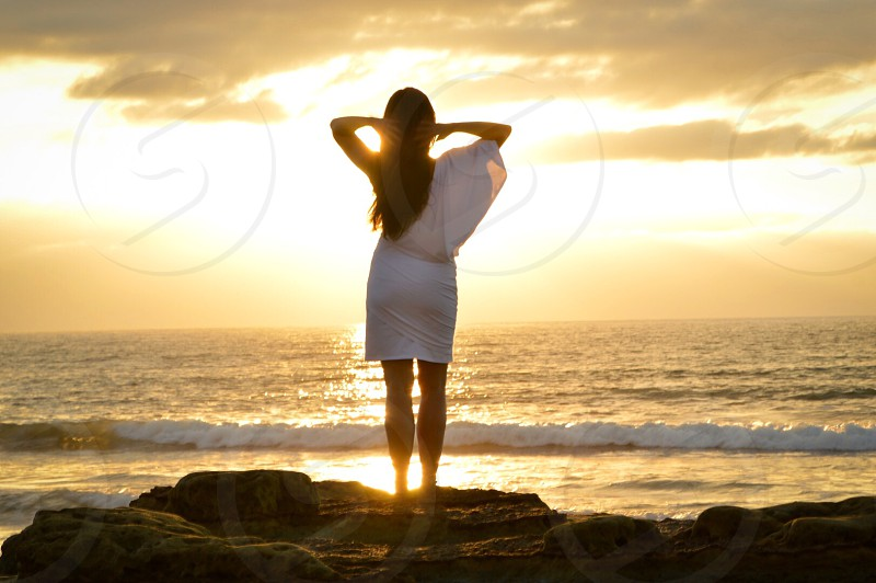 woman in white sundress facing the ocean photo