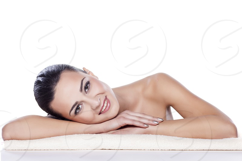portrait of a beautiful girl lying on a towel on a white photo