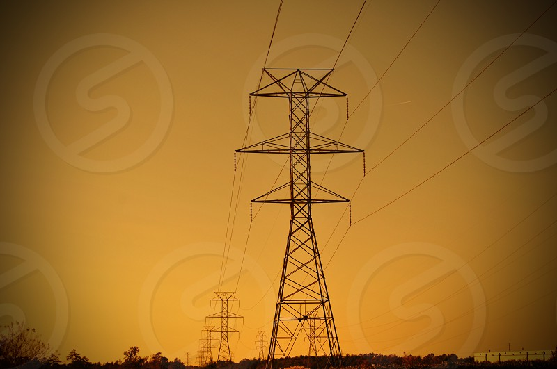 Electricity pylons against a golden sky with a vignette  photo