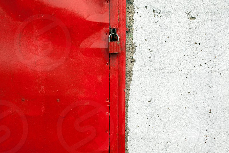 Texture of an old red door closed with padlock closeup view.  photo