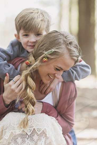 blonde woman with small blond boy hugging her from behind photo