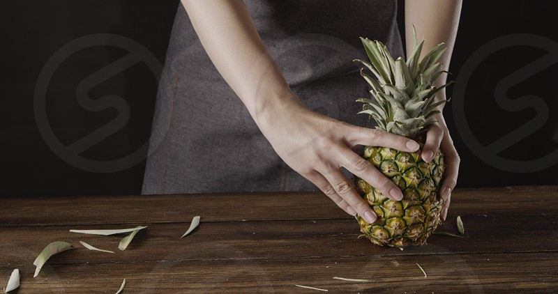 Girl's in a textile apron holds fresh ripe juicy natural organic texoticl fruit pineapple on a wooden kitchen table on a black background. Concept of vegetarian diet eating. photo