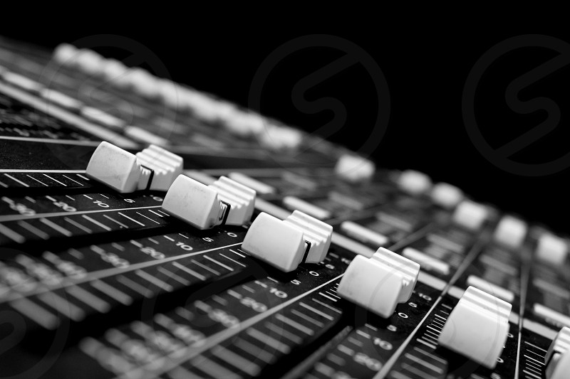 Wide angle closeup of Pro Audio Digital Mixing Console. White Faders and black control Console photo