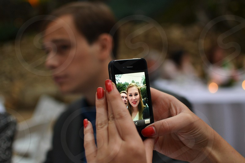 woman with red manicure holding phone with woman on screen photo