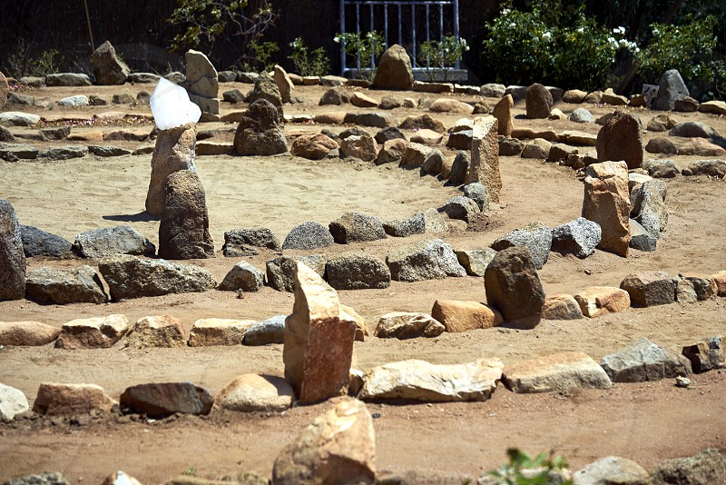 Large stone and sand labyrinth bathed in mid-day sunlight; crystal center stone to gather your thoughts photo