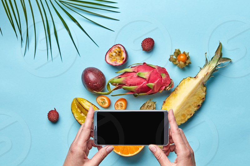 Set of different tropical fruits and palm leaf on a blue phonet with space for text. Woman's hand is holding a mobile. The concept of buying products online. Flat lay photo