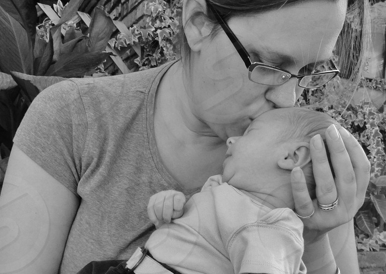 brunette woman kissing forehead of sleeping baby photo