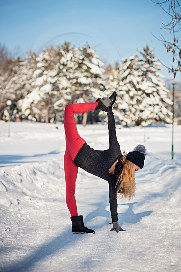 Beautiful woman doing yoga outdoors in the snow at winter time photo